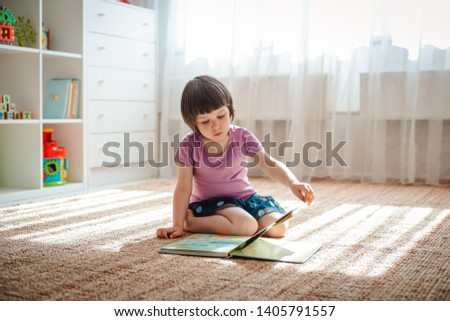 little girl 3 years old child is reading a book sitting on the floor in the room. Early childhood development