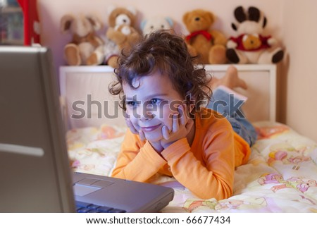 little girl, 5- 6 years old, enjoying her favorite cartoon on a laptop