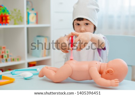 Little girl 3 years old preschooler playing doctor with doll. The child makes an injection toy. The concept of childhood vaccinations. Childhood in kindergarten role-playing educational games