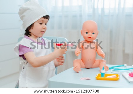 Little girl 3 years old preschooler playing doctor with doll. The child makes an injection toy. The concept of childhood vaccinations. Childhood in kindergarten role-playing educational games #1512107708