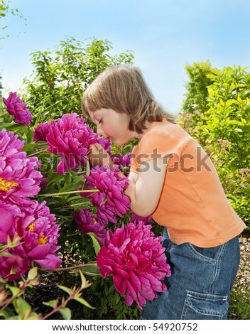 little girl 3 years old smelling to flowers