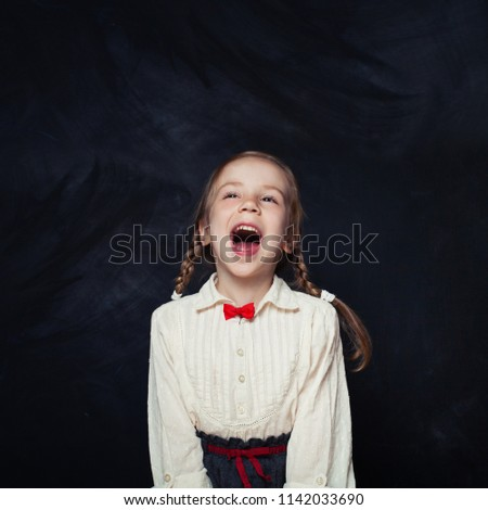 Little girl yelling and having fun. Happy child on empty blackboard background with copy space. Back to school sale concept #1142033690