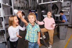 Little girl yelling at boy reaching for something in closed quest room stylised as abandoned bunker