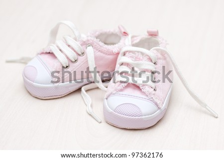 little girlie baby shoes on a wooden floor