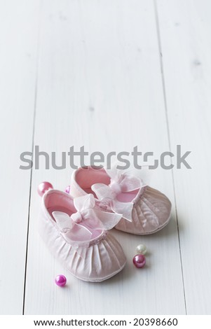 little girlie baby shoes on a wooden floor, copy space for text, perfect for invitation or card