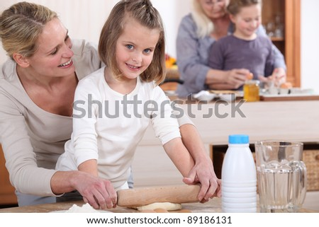 Little girls and their mums making cakes