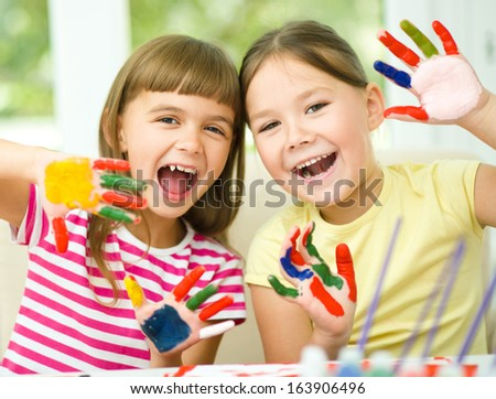 Little girls are painting with gouache and showing their painted hands while sitting at table