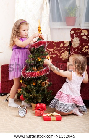 little girls at a Christmas fir-tree.