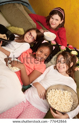 Little girls at a sleepover eat popcorn and tortilla chips