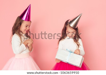 Little girls birthday studio isolated on pink wall girl opening present excited