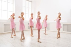 Little girls dancing ballet in studio. Choreographed dance by a group of graceful pretty young ballerinas practicing during class