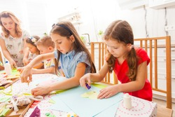 Little girls do applique work together with a teacher