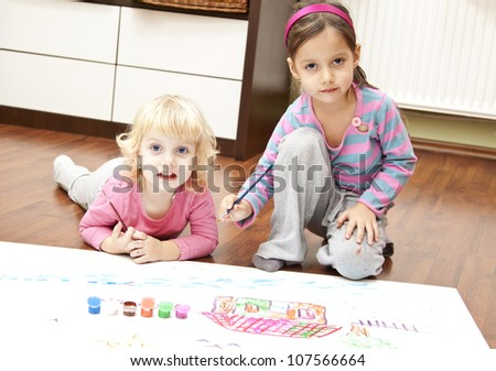Little girls drawing pictures to Santa Claus to get christmas gifts. Indoor at home