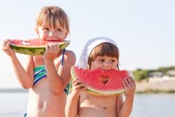 Little girls eat watermelon on the beach