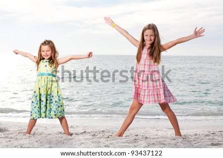 Little girls enjoy summer day at the beach.