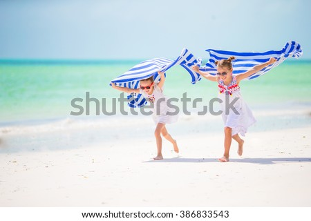 Little girls having fun running with towels on tropical beach