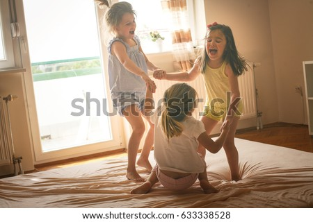 Little girls having fun together in bed. Little girls playing at home on bed.