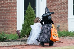Little girls in witch and ghost costume having fun at Halloween trick or treat