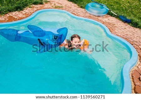 little girls is swimming in the pool by a summer day #1139560271