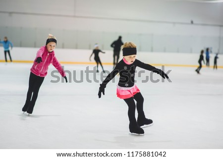 Little girls learning to ice skate. Figure skating school. Young figure skaters practicing at indoor skating rink.