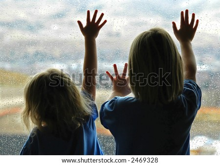 Little girls looking out window on a rainy day