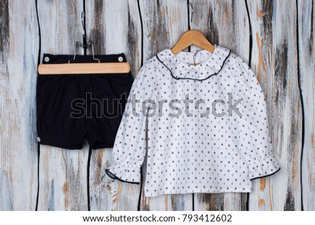 Little girls pajama set. Navy shorts and white long sleeve top with nautical pattern. Sleeping garments on wooden hangers. #793412602