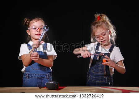Little girls play in the construction profession, a wrench in his hands. The concept of children's games in adult professions. #1332726419