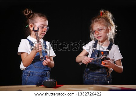 Little girls play in the construction profession, a wrench in his hands. The concept of children's games in adult professions. #1332726422