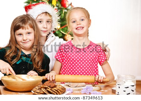 Little girls rolling dough to make Christmas cookies
