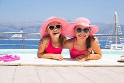 little girls sitting on the beach and sunbathe in the sun