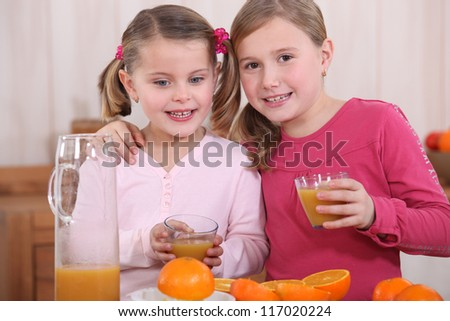 Little girls squeezing oranges
