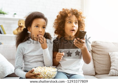 Little girls watching discovery channel and eating popcorn, sitting on sofa at home