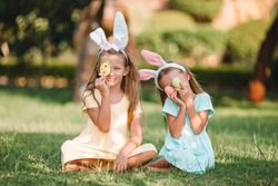 Little girls wearing bunny ears on Easter holliday, having fun and smiling