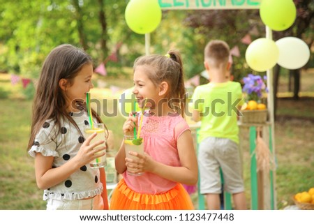Little girls with natural lemonade in park #1123477448