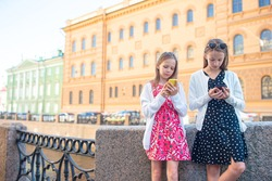 Little girls with smartphone at the summer waterfront in Saint Petersburg