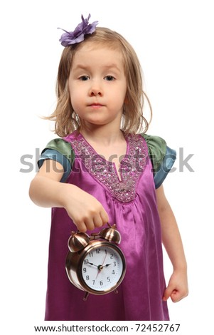 Little glamour girl in stylish dress shows time on round alarm clock