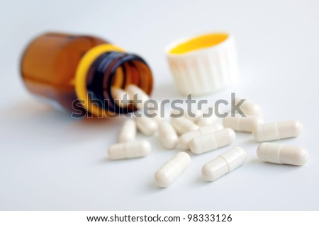 Little glass bottle with white pills spilled over a table