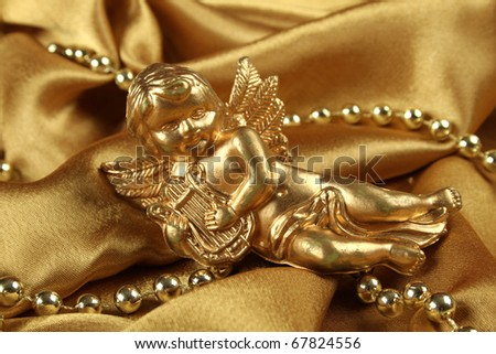 Little gold angel with a harp lying on the golden cloth beside ornaments. Background