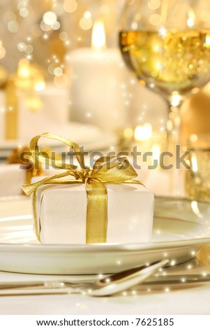 Little gold ribboned gift with gold background