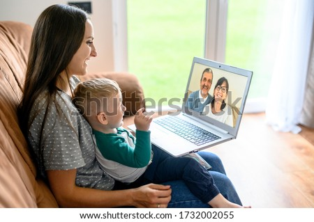 Little grandson is talking via video call on laptop with a grandparents. A young mother with a baby son sit on a sofa at home and have a video meeting, grandparent are on a laptop screen