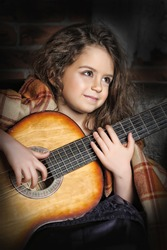 Little gypsy girl with a guitar in her hands