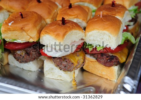 Little hamburgers with lettuce, tomato and cheese ready to serve