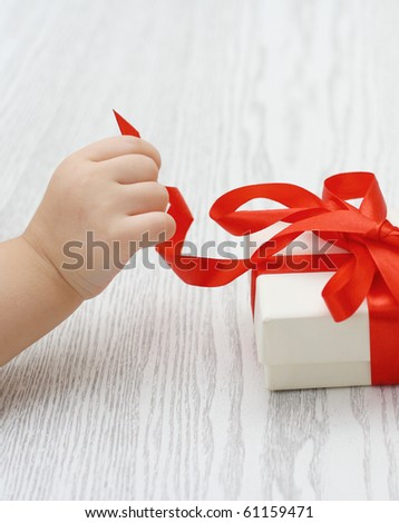 Little hand of the child opening a gift - stock photo