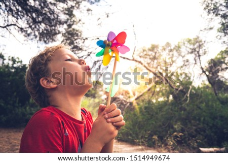 Photo of  Little handsome boy blows a pinwheel in a forest, carefree, with faded tones and retro style.