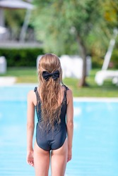 Little happy adorable girl in outdoor swimming pool. Back view of adorable kid in black