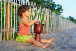 Little happy baby girl play ethnic music on traditional african hand drum djembe, enjoying sunset on ocean beach. Children healthy lifestyle. Travel, family activity on tropical island summer holiday.