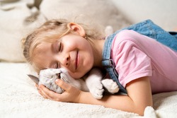 Little happy blonde girl lies on the bed and hugs a white sleeping kitten and smiles closing her eyes.