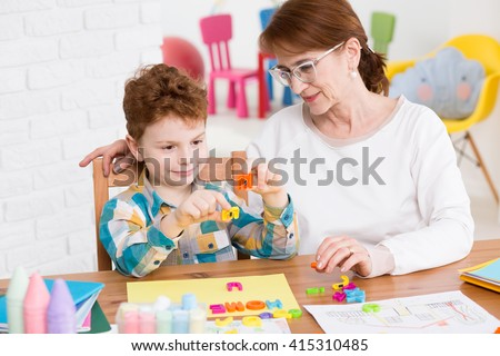Little happy boy having classes with occupational therapist. Setting words from colorful letters