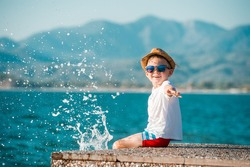 Little happy boy in blue sunglasses and hat has a big smile on his face. Beautiful landscape and bright beach. Blue summer sky and sea water background. Kid on summer vacation. text. copy space