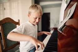 little happy boy plays piano at home